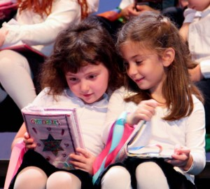 First graders Yael Mainzer and Natalie Grosswald admire their new siddurim. PHOTO / GHA