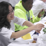 Suji Ham, a Korean exchange student from Faith Lutheran School of Marietta, takes some parsley as part of the Interfaith Seder.