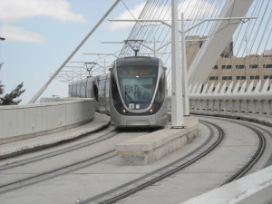 "A train, part of Jerusalem's new light railway, crosses the ""Bridge of Strings"" just past the city's Central Bus Station. PHOTO / JNS.org"