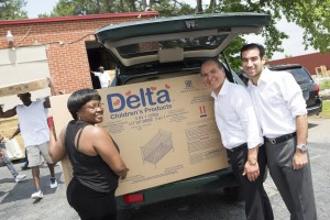 Delta Children president Joe Shamie and son David (center and right) help deliver cribs at Caring For Others, Inc.