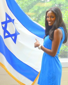 Yitayish Ayenew, the first black Miss Israel and also the first woman of Ethiopian heritage to win the crown, poses with the Israeli flag at Solomon Schechter Day School of Bergan County, NJ, on June 14. Credit: Maxine Dovere.