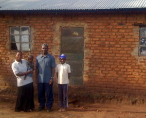 Moses Sebagabo in front of his home in Mbale, Uganda with his wife, Esther Kasuubo; daughter, Ora Naula; and son, Yonatan Chani.