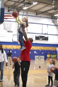 Hawks assistant coach Dedric Willoughby holds up Epstein first-grader Kayla Furie for a dunk while classmates Iian Bachar and Abby Hanna watch.