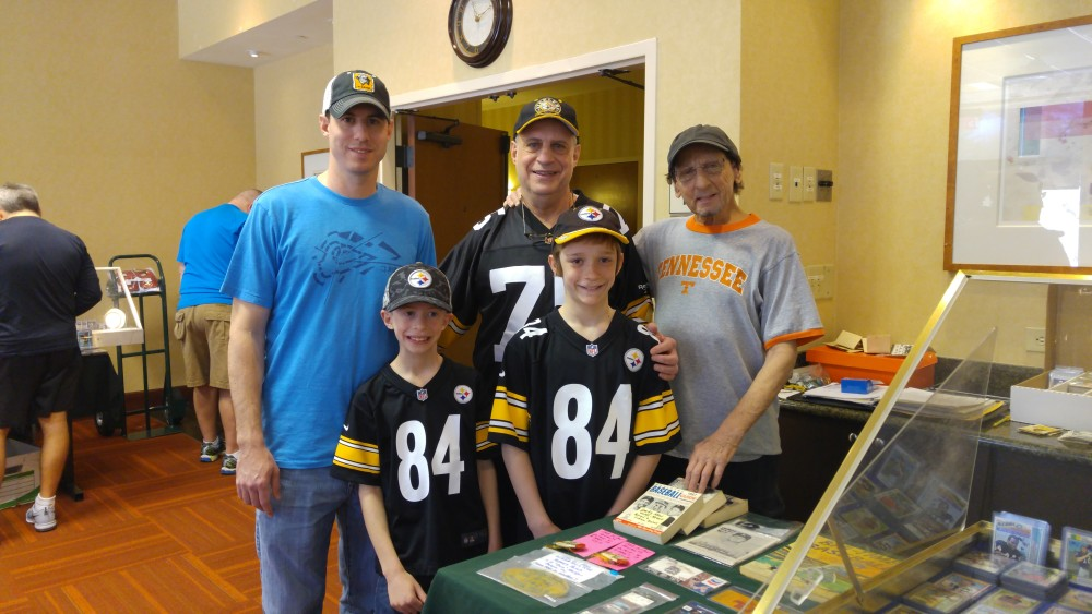 Frank Moiger (right) welcomes a longtime customer and friend, Harvey Linder, to one of his sports collectible shows. With Linder are his sons, Zal (back left), Aiden (front left) and Aaron.