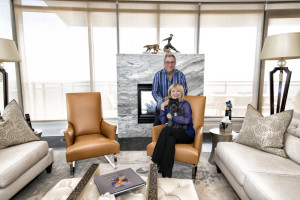 Donna and Michael Coles pose with Journey on one of their dark mustard Donghia leather chairs.