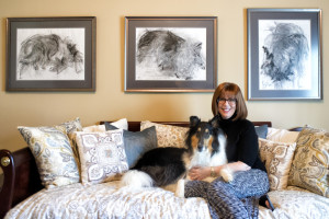 Beth Shapiro poses with Luna under a charcoal triptych of the collie.
