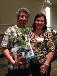Jason and Sandrine Simmons prepare to leave with their MAZON tzedakah box tomato plant and haggadah.