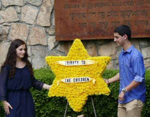 BBYO members Anna Jackson of Chattahoochee High School and Charlie Burstiner of Walton High School place the special floral star marking the ceremony's focus on the children of the Holocaust.
