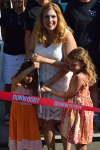 Matilda and Ruby Mundell help their mother Sally Mundell, cut the ribbon outside the Packaged Good on July 2.
