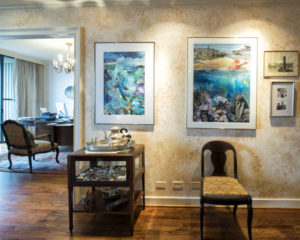 The front entrance welcomes guests with Luciana Foah's oils and an antique abalone umbrella stand.