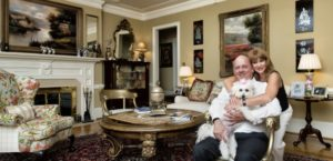Renee and Charles Evans with pup Princess Winifred enjoy their formal living room amid European oils, Persian silk carpets, Vietnamese mother-of-pearl lacquer panels and an antique Prussian royal egg.