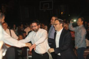 With Rabbi Adam Starr behind him, Rabbi Eli Lob reaches out to Rabbi Ilan Feldman during the dancing. (Photo by R.M. Grossblatt)
