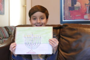 Fourth-grader Ari Gordon, 10, poses with his prize-winning Chanukah drawing.