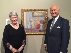 "Collectors Sandy and Bob London flank their 1981 painting by Barton Church, ""The Red Pot,"" known for its gentleness and sense of monumentality."