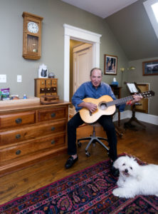 Walt Myers poses with his guitar by a clock, pet food cabinet and chest he designed.