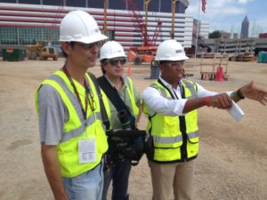 David Lewis and Michael Epstein get direction from Darden and co. project manager Whitney Williams at the construction site of Mercedes-Benz Stadium.