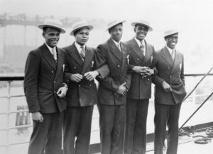 "Photo courtesy of Olympic Pride, American Prejudice LLC Steaming to Europe on the SS Manhattan in July 1936 are (from left) James LuValle, the bronze medalist in the 400 meters; Archie Williams, the gold medalist in the 400; John Woodruff, the gold medalist in the 800; Cornelius Johnson, the gold medalist in the high jump; and Mack Robinson, the silver medalist in the 200. Their story is told in ""Olympic Pride, American Prejudice,"" showing Jan. 27, Feb. 5 and Feb. 9."