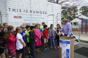 "Rabbi Brian Glusman discusses hunger with elementary school children outside the ""This Is Hunger"" mobile exhibit."