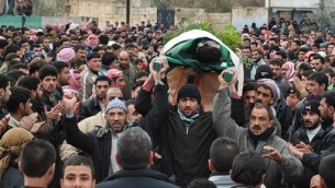 In this photo taken earlier this month, anti-Syrian regime protesters carry the body of a man, who witnesses say was killed by Syrian government forces' shelling, during a funeral procession in the Rastan neighborhood of Homs province. (AP Photo)