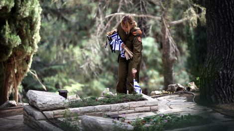 An IDF soldier places Israeli flags on the graves of fallen soldiers on Mount Herzl in Jerusalem (photo credit: Yossi Zamir/Flash 90)