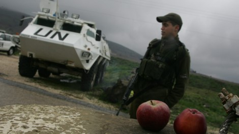 An IDF soldier oversees the delivery of apples from Israel to Syria through the Kuneitra checkpoint in 2007 (photo credit: Haim Azulay/Flash90)