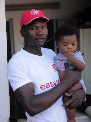 Augustine, a Nigerian migrant, with his son in front of their Tel Aviv home, which also serves as a kindergarten for African children. The house was recently the target of a Molotov cocktail attack (photo credit: Tomer Neuber