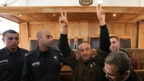 Marwan Barghuti is escorted in handcuffs into Jerusalem's Magistrates Court in January 2012 (photo credit: Flash90)