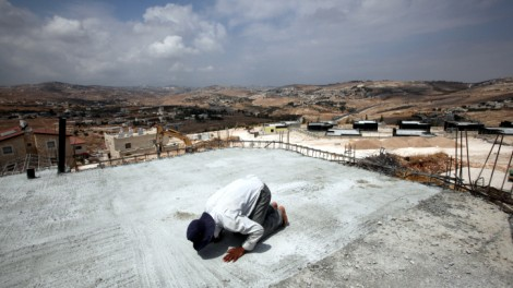 A Palestinian construction worker prays on the roof of a house that is being built in the West Bank settlement of Tekoa (photo credit: Yossi Zamir/Flash90)