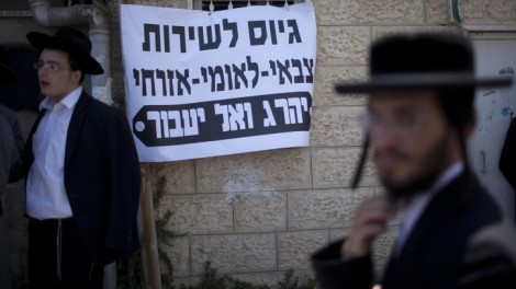 "Ultra-Orthodox men protest against the universal draft initiative. The sign reads, 'It is better to die than to transgress the prohibition against joining the army, civic service or national service."" (photo credit: Yonatan Sindel/Flash90)"