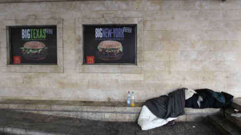 A homeless man sleeps on the street outside of a McDonald's restaurant in Jerusalem (photo credit: Nati Shohat/Flash90)