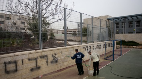A rising tide of hatred. At the Jewish-Arab bilingual school in Jerusalem, workers clean off graffiti stating &quot;death to arabs&quot; and &quot;Kahana was right,&quot; February 2012. (photo credit: Flash90)