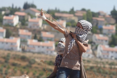 A Palestinian demonstrator hurls a stone at Israeli border police officers during a protest in Nabi Saleh. The Jewish settlement of Halamish can be seen in the background. (photo credit:Issam Rimawi/flash90)