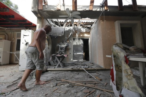 An Israeli man examine a house in southern Israel that was damaged by a rocket fired by Palestinians in Gaza, Wednesday, October 24, 2012 (photo credit: Tsafrir Abayov/Flash90)