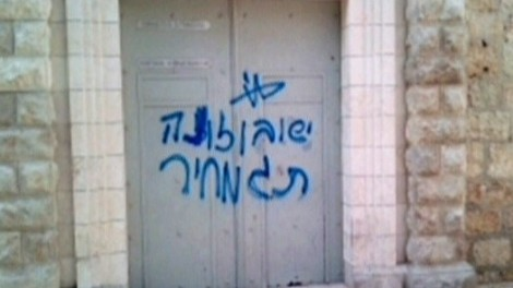The phrases 'Jesus is a son of a bitch' and 'price tag,' spray-painted on the wall of a Jerusalem church (photo credit: Channel 2 News)