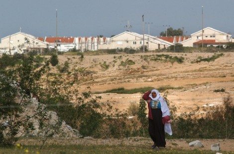A Palestinian woman walks past the Jewish settlement of Netzarim, 2004 (file photo: Sharon Perry/Flash90)