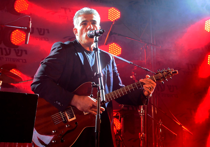 What if he isn't bluffing? Yair Lapid plays the guitar at a party celebrating Yesh Atid's election success (photo credit: Flash90)