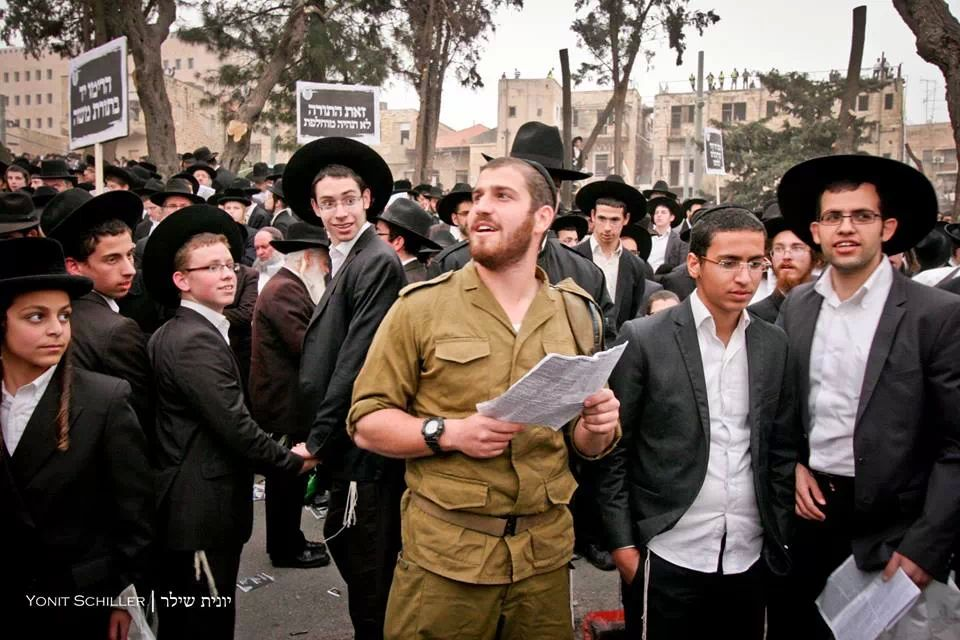A beautiful, yet isolated,  moment of unity wherein a religious IDF soldier chose to catch afternoon prayers at the haredi prayer rally.  Photo credit: Yonit Schiller