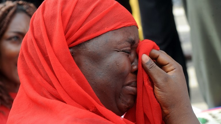 One of the mothers of the missing Chibok school girls wipes her tears as she cries during a rally by civil society groups pressing for the release of the girls in Abuja on May 6, 2014 (Photo credit: Pius Utomi Ekpei/AFP)