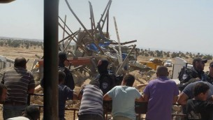 Residents of El Araqib look on as the authorities demolish their village