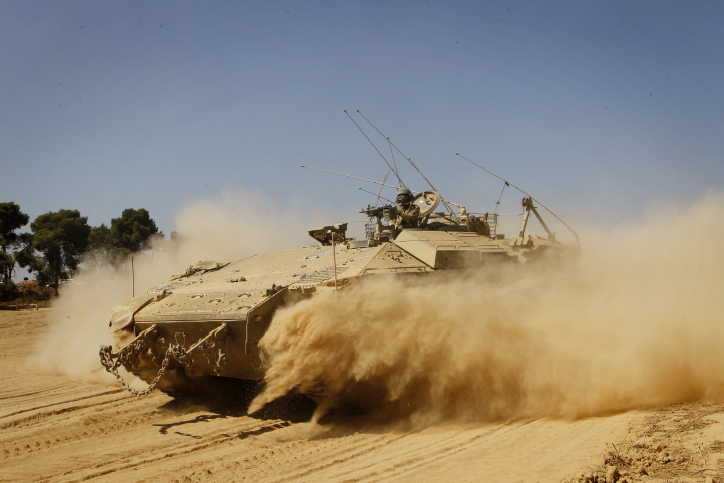 An IDF armored personnel carrier seen crossing through a field near the Israeli border with Gaza. (photo credit: Miriam Alster/FLASH90)