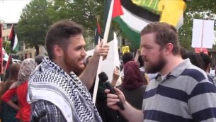 A man explains why he is waving a Hezbollah flag in Washington DC.  12th July 2014