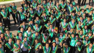 Students posing with three fingers held up.  On their graduation they are celebrating not the beginning of their new lives but the end, the deaths of three Israeli teens.