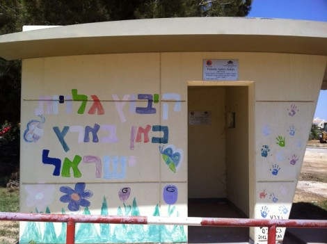 "Concrete bus stop bomb shelter at Kibbutz Alumim for kids waiting to be picked up for school. Writing: ""Ingathering of the Exiles, Here in the Land of Israel"" (photo credit: Gavin Gross)"