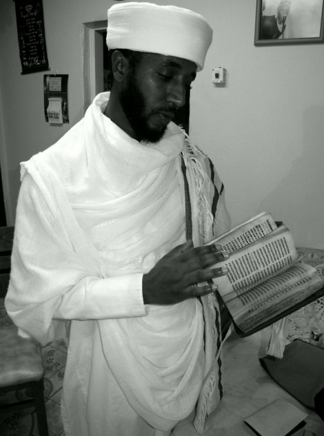 Qes Efraim Zion-Lawi, the first Israeli-born qes, holds a Jewish book written in Ge'ez that was concealed by his parents while they were in Sudan prior to reaching Israel. Photo - Shai Afsai