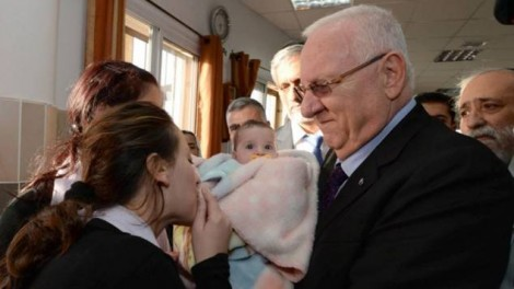 Reuven Rivlin holds the baby daughter of slain police officer Zidan Saif