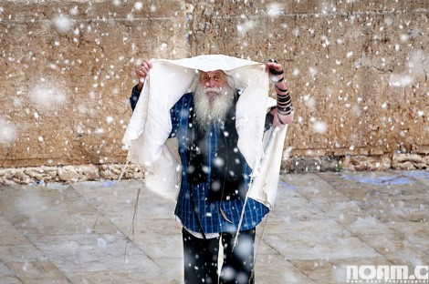 man hiding from snow with prayer shawl