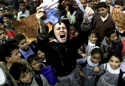 Rachel Corrie at a rally in southern Gaza, burning a mock U.S. flag in a crowd of Palestinian Children (Associated Press)
