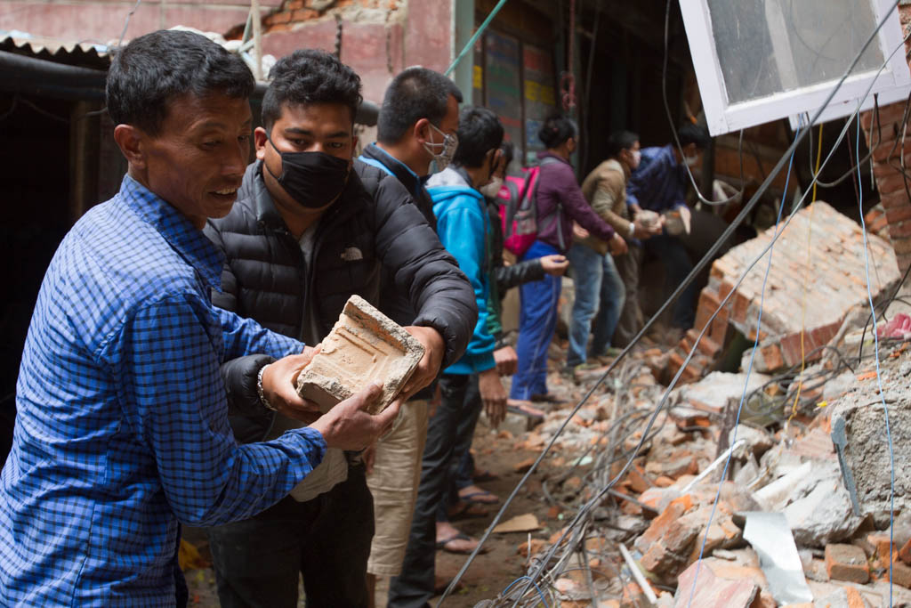 A sponeous community of local volunteers assists with the clearing of rubble.