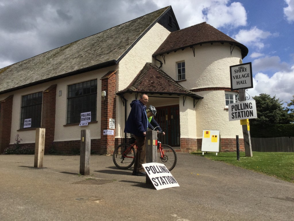 Two older men chat in front of a village hall with 'POLLING STATION' signs.