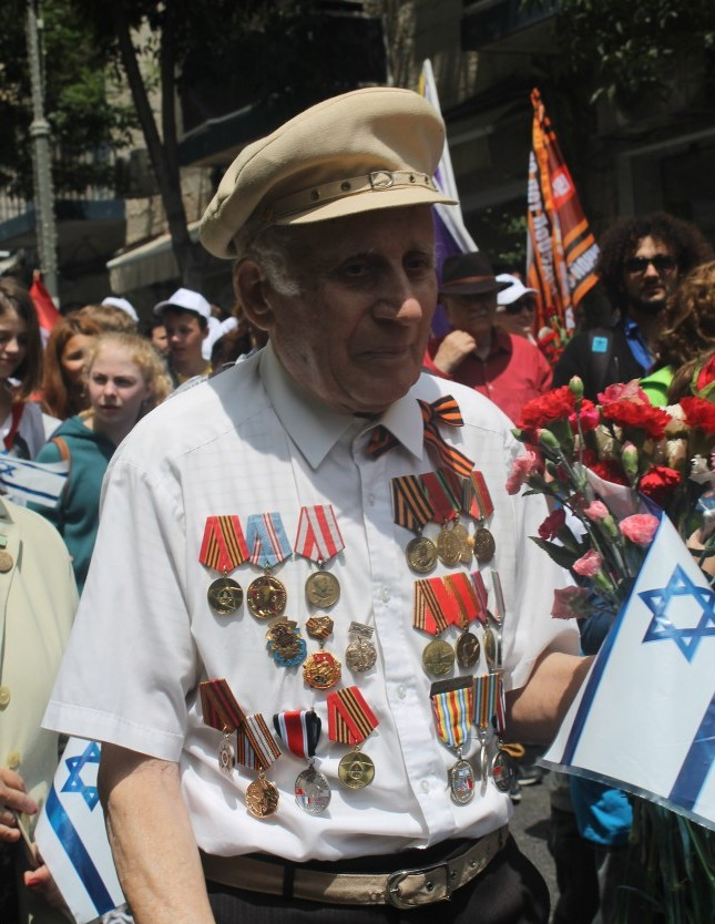 Surrounded by Israeli flags and red carnetias, a Soviet V-Day symbol, the veterans demonstrated both their particular WW2 heritage and their conviction that it is part of Israels story